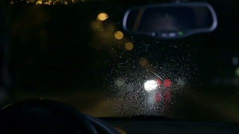 Unfocused shot through windscreen on rainy night Live Action