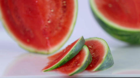 Holding watermelon vertically and slicing it with  Live Action