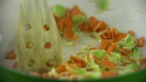 Stirring vegetables around dish Live Action
