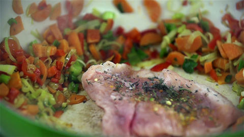 Throwing spiced up steak in oiled up dish with veg Live Action