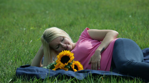 Preagnant woman stroking her stomach in the park Footage