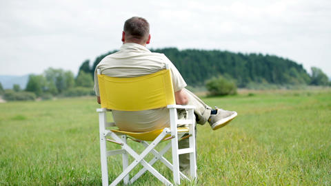 Man Sits On A White Picnic Chair And Observes The  stock footage
