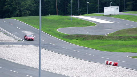 Red racing car speeding and turning on a race-trac Footage