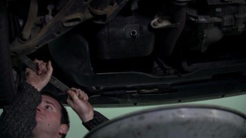 Mechanic fixing bottom of car's chassis Footage
