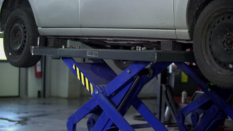 Side Shot Of Lowering The Car On A Lift In A Worsh stock footage