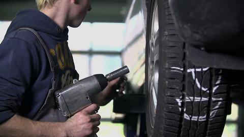 Pan shot of mechanic loosening the car's tire Footage