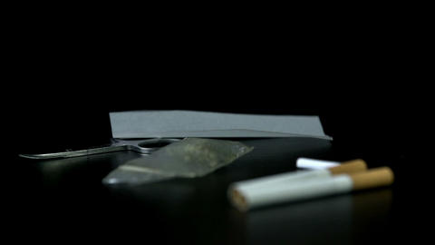 Putting a smoking paper next to cigarettes and a p Footage