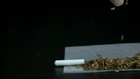 Scattering tobacco from cigarette on a rolling pap Live Action