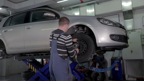 Vulcaniser removes a tire from a car raised high a Footage
