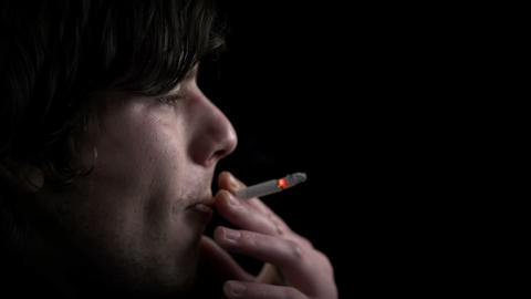 Side shot of young man inhaling a cigarette smoke  Footage