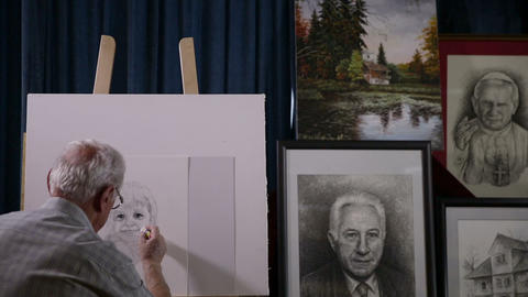 Slow pan shot of painter's work and him at work Footage