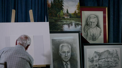 Artist Drawing Among His Completed Works stock footage