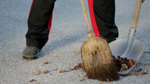Man sweeps leaves onto the shovel and emptys it in Live Action