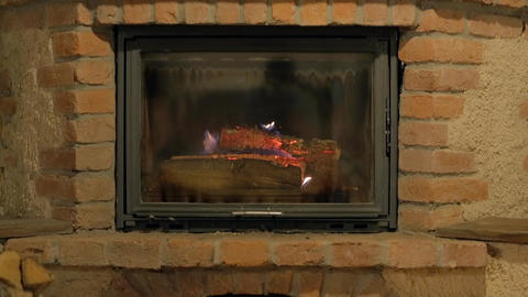 Tilt shot of an old fireplace with burning logs Footage