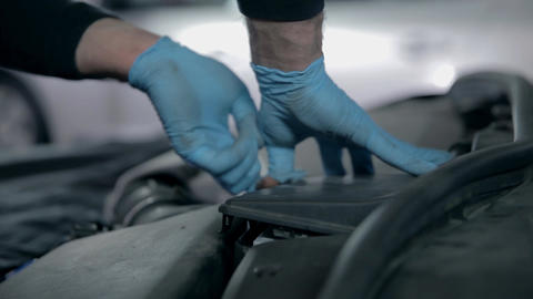 Mechanic is placing parts back in their place Live Action