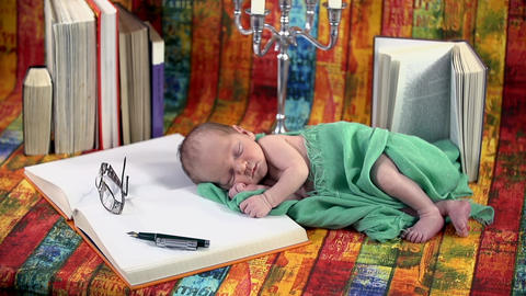 Baby sleeping on a book next to a candlestick Footage