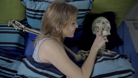 Young woman wakes up in bed next to a skeleton and Footage
