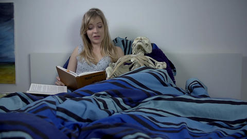 Woman reads out loud to the skeleton in her bed Footage