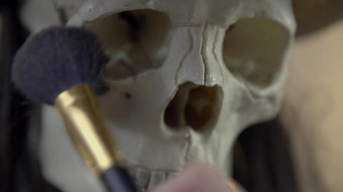 Close Up Of Putting Make Up On A Skull stock footage