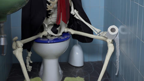 Skeleton sitting on the toilet with a toilet paper Footage