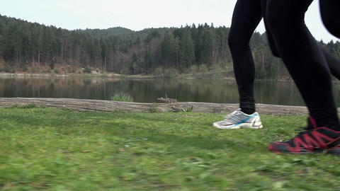Side Shot Of Two Runners At Lake In Slow Motion Footage