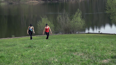 Two Attractive Woman Walking Uphill At Lake In Slo Footage