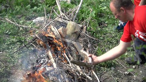Man putting wood on bonfire Footage