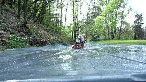 Man sliding through water slide Live Action