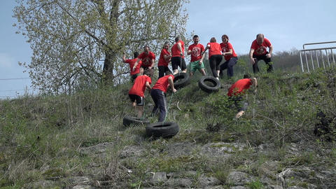 Team Dragging Car Tires Up The Hill stock footage