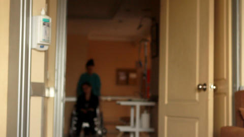 nurse carrying patient on a wheelchair Stock Video Footage