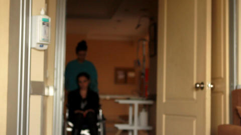 nurse carrying patient on a wheelchair Footage