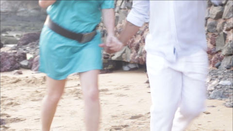 man and woman going through sand on the beach near Footage