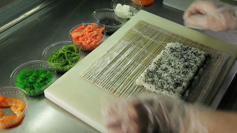 Cook making sushi rolls, spreading rice over nori Footage