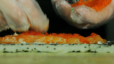 Chef adding tobiko to sushi rolls, close up view Footage