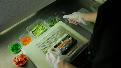 Chef adding salmon and cucumber to sushi rolls Footage