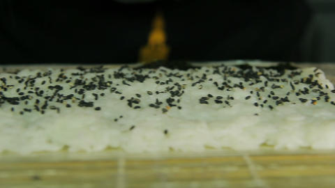 Chef adding sesame to sushi rolls Footage