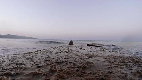 Calm sea waves lapping against flat rock Footage