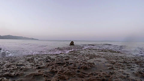 Calm Sea Waves Lapping Against Flat Rock 4x Speed stock footage