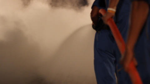 A team of fire fighters hold a hose and put out a Footage
