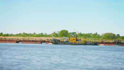 Tug Boat floats on the river past the dredger Footage
