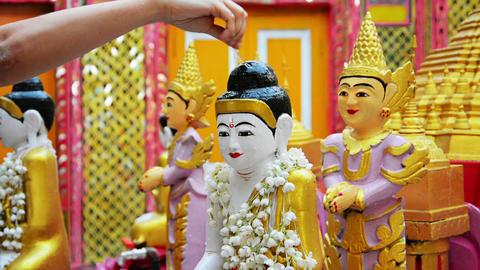 Watering Buddha figurine. Ritual in the Buddhist t Footage