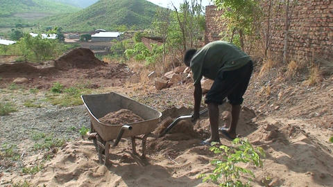 Malawi: african man fills the barrow with sand Stock Video Footage
