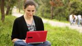Beautiful Girl Using Computer In Countryside, Phaeton Passing Behind stock footage