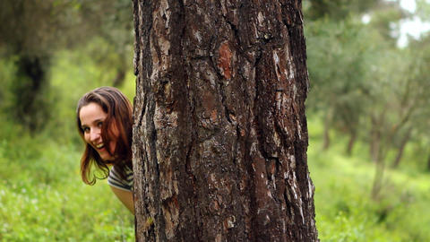 beautiful girl looking at the camera behind tree Stock Video Footage
