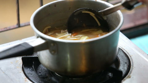 stirred ladle chicken soup in saucepan on gas stov Footage