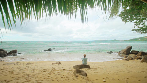 A lone man sits on the shore of a tropical ocean Footage