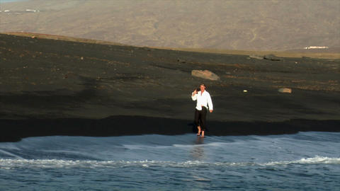 business man enjoy walking black lava beach Stock Video Footage
