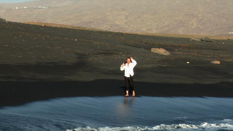 business man enjoy walking black lava beach Footage