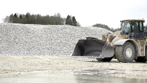 A slow moving bulldozer with stones at the back Footage