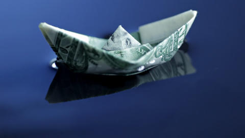 Origami boat made of dollar bill floating Footage